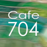 Cafe 704 written over green movement blurred tiles